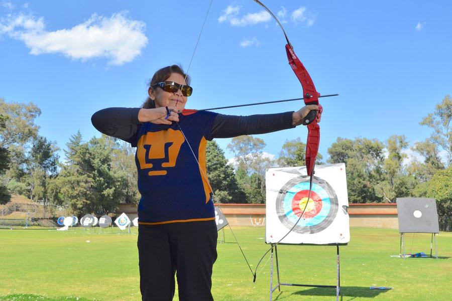 Maestra Cati arquera de tacto posa con arco y flecha representando al equipo especial de la Universidad nacional Autónoma de México UNAM